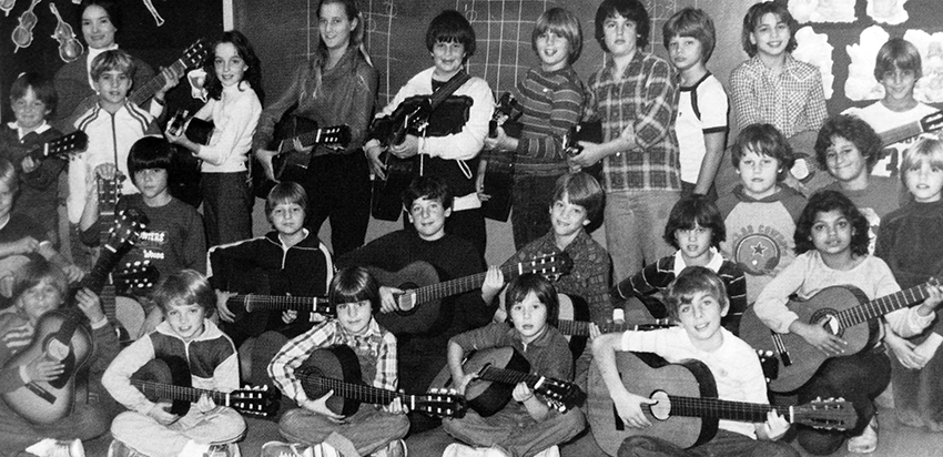 Black and white photograph from our 1980 to 1981 yearbook showing students in the Guitar Club. 23 students and their teacher sponsor are shown. The children are mostly boys. Almost every child in the photograph is holding a guitar.