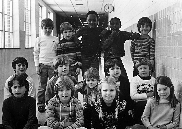 Black and white photograph of students in a hallway at Hunters Woods Elementary School. 14 children are pictured, mostly boys. Based on the clothing the children are wearing, the picture was taken around 1979 or 1980. A clock is visible in the distance. The photograph was taken at 11:40 a.m.
