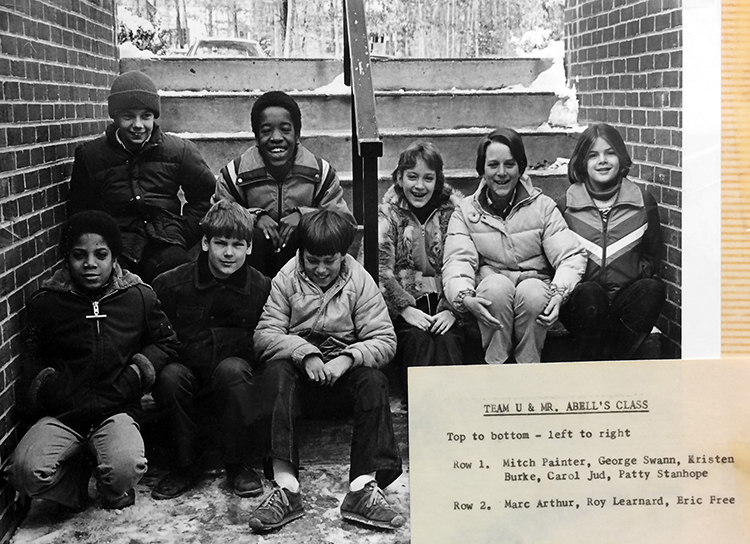 Black and white photograph of a group of students who have been inducted into the Reading Hall of Fame. The photograph was part of a scrapbook collection in our library and has a card listing the students' names. The card reads: Team U and Mr. Abell's Class. Top to bottom – left to right. Row 1: Mitch Painter, George Swann, Kristen Burke, Carol Jud, Patty Stanhope. Row 2: Marc Arthur, Roy Leonard, Eric Free. The students are pictured sitting in a stairwell outside the building. They are wearing heavy jackets and snow is visible on the ground behind them.