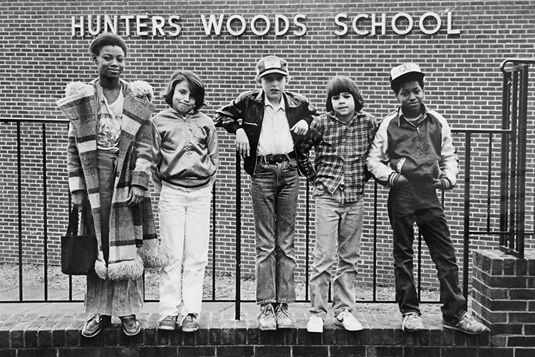 Black and white photograph of five students standing on the brick wall in front of our school and leaning on the metal railing. The name Hunters Woods School is visible behind them on the building.