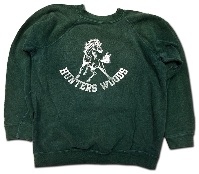 Photograph of a sweatshirt donated to our school by a parent of a former student. The fabric is dark green in color and has an illustration of a mustang and the words Hunters Woods printed in white on the chest.