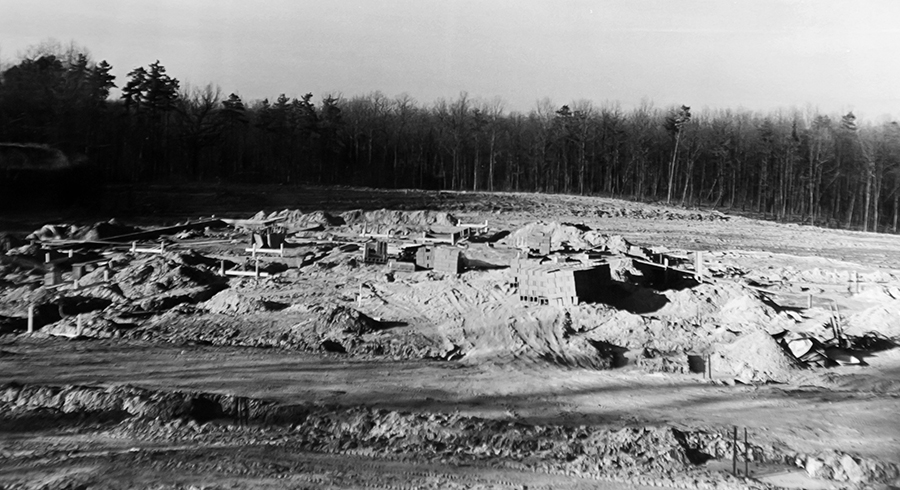 Black and white photograph, taken in 1969, showing the Hunters Woods site during the earliest stage of construction. No walls are visible. The outline of the foundation is in place and there are stacks of cinderblocks waiting to be used. The dirt around the site is piled into large mounds. There are trees visible in the distance.