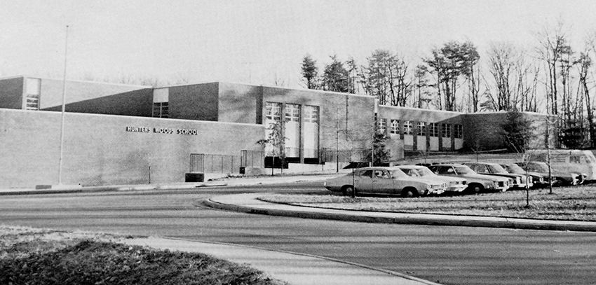 Black and white photograph of the front of Hunters Woods Elementary School that appeared in our 1975 to 1976 yearbook. The photographer is standing on the sidewalk next to Colts Neck Road and is looking up the hill toward the school. Several young trees have been planted on the grounds and a row of cars is parked in front of the building along the driveway loop.