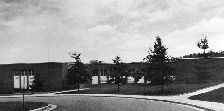 Black and white photograph of Hunters Woods Elementary School from our 1978 to 1979 yearbook.  There are three trees planted along the sidewalk in an area that will become a new main entrance to the building in 2003. The original main entrance can be seen down the hill on the left.
