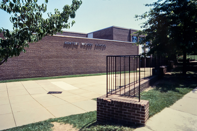 Undated color photograph of Hunters Woods Elementary School from a 35 millimeter slide. The picture was taken from the sidewalk leading toward the building's original main entrance. The name Hunters Woods School is visible on the side of the building.