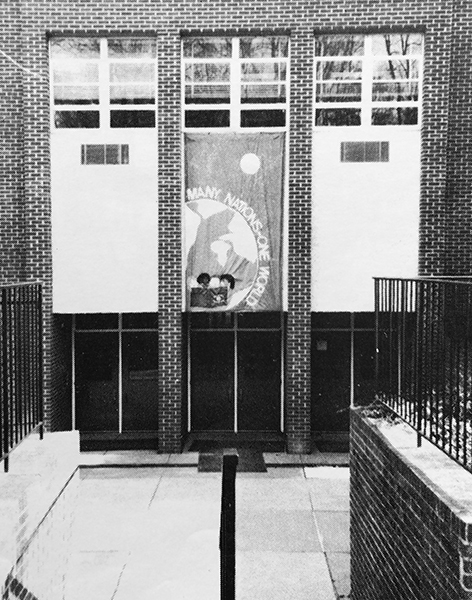 Black and white photograph of the original main entrance to Hunters Woods. It comes from our 1990 to 1991 yearbook. There are three sets of doors, and a banner is hung above the middle door. It is printed with a graphic representation of the Earth and has text that reads: Many Nations – One World.
